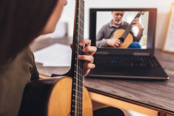 Happy little girl learning to play guitar while watching lessons at laptop at home stock photo