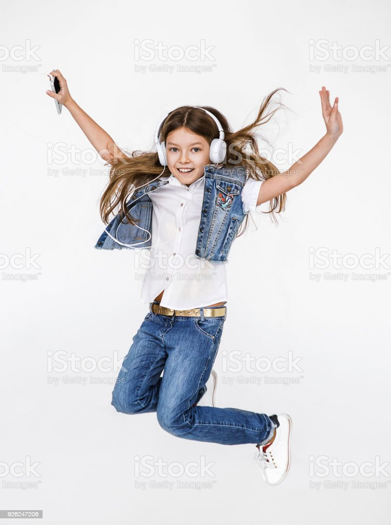 Happy little girl listening music, jumping and having fun stock photo