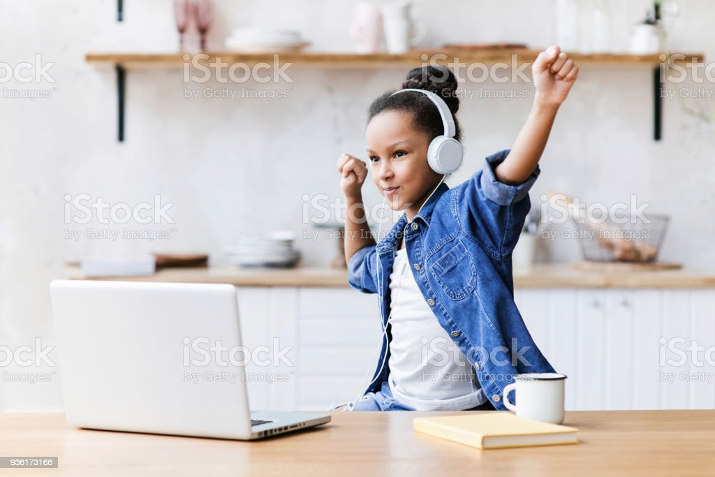 Happy little girl listening to music and having fun stock photo
