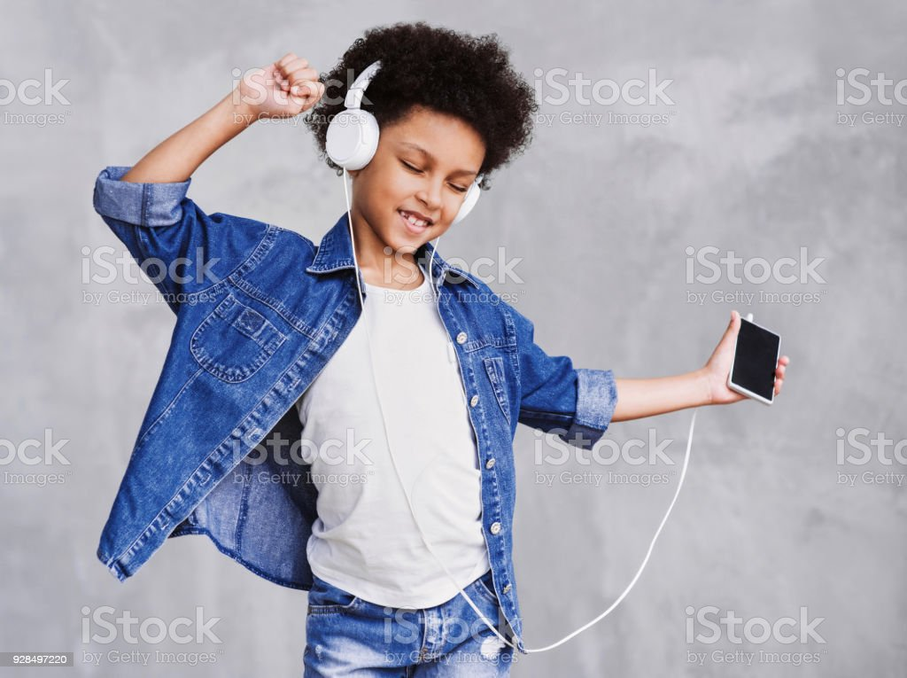 Happy little girl listening to music, dancing and having fun stock photo