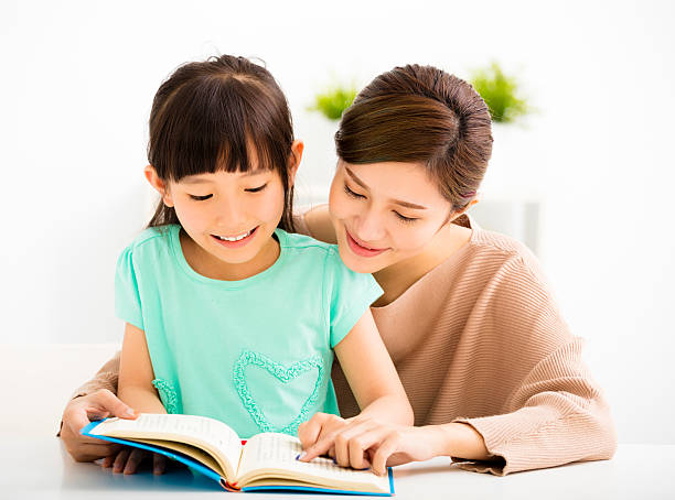 happy Little girl looking at book  with her mother stock photo