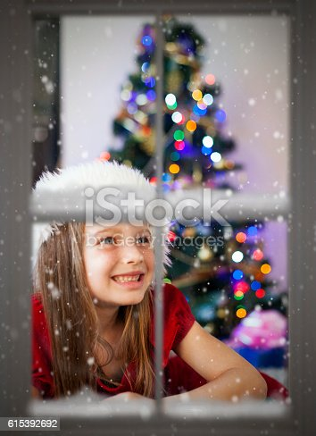 istock Happy little girl looking through snowy window at Christmas 615392692