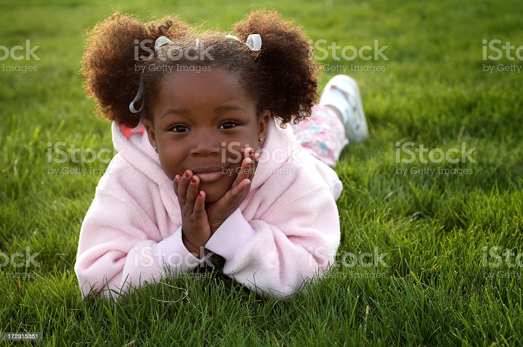 Happy Little Girl Lying in the Grass royalty-free stock photo