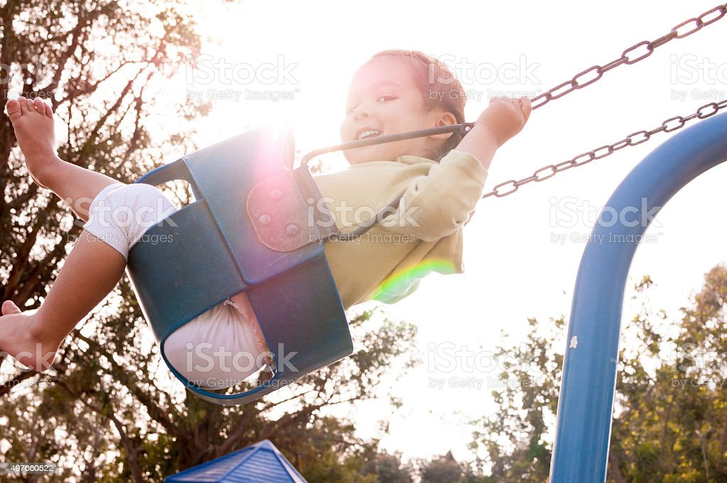 Happy little girl on swing at playground stock photo