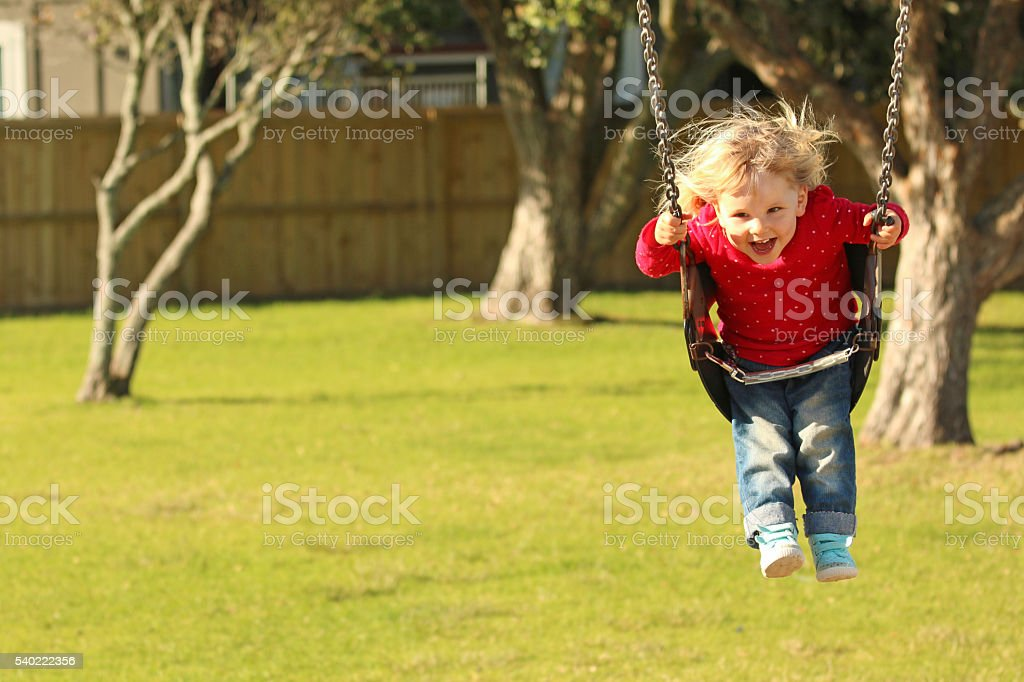 Happy little girl on swing stock photo