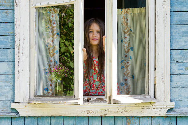 happy little girl opens a window the early sunny morning - lüften stock-fotos und bilder