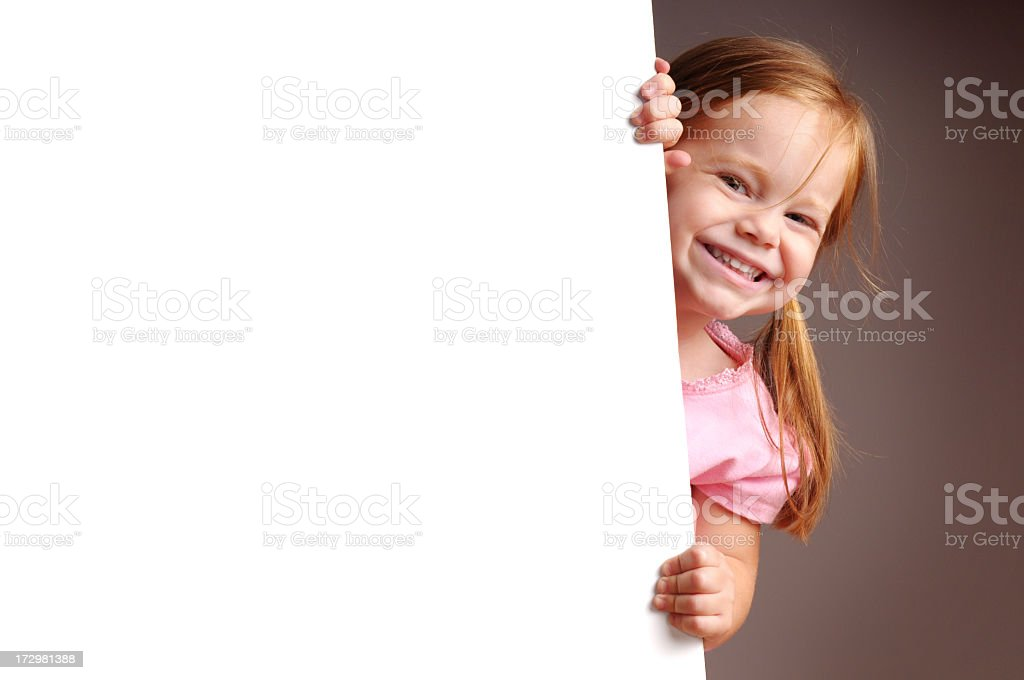 Happy Little Girl Peeking from Behind Blank Sign royalty-free stock photo