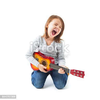Happy little girl kneeling on her knees playing acoustic guitar  with her mouth wide open and eyes closed. She is isolated on white background.