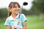 Happy little girl playing golf at country club
