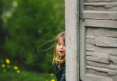 Happy little girl playing hide and seek. Kid peeking out of her house in a village