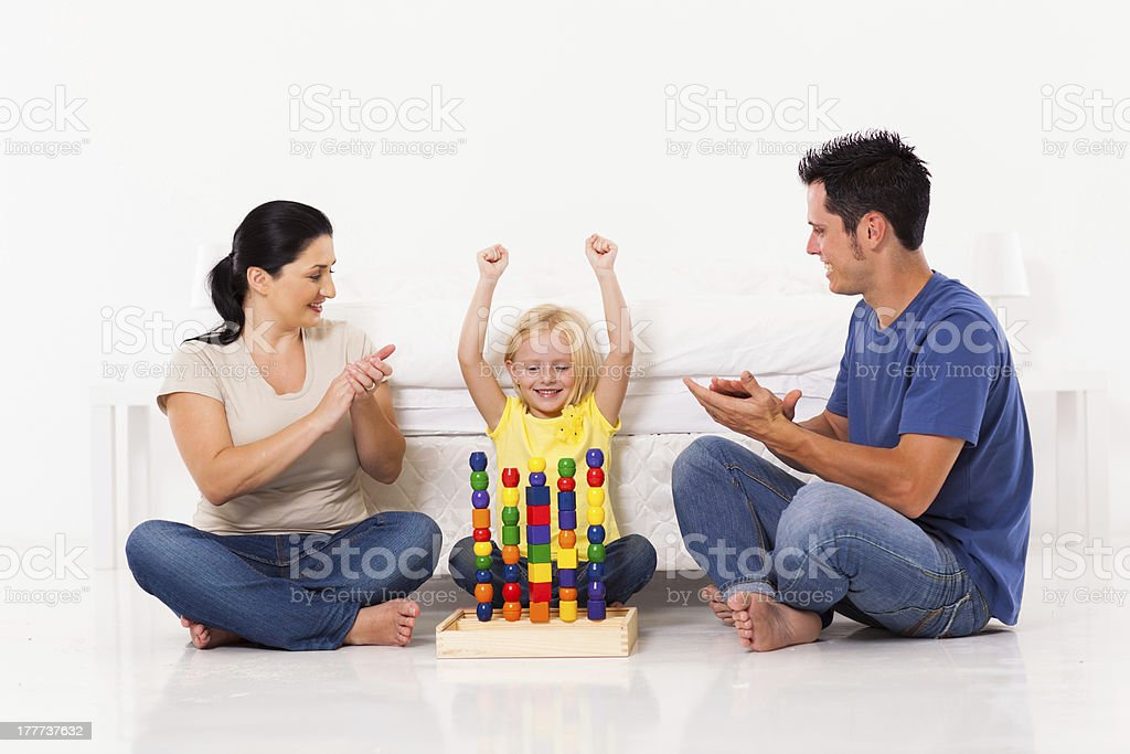 happy little girl playing toys with parents royalty-free stock photo
