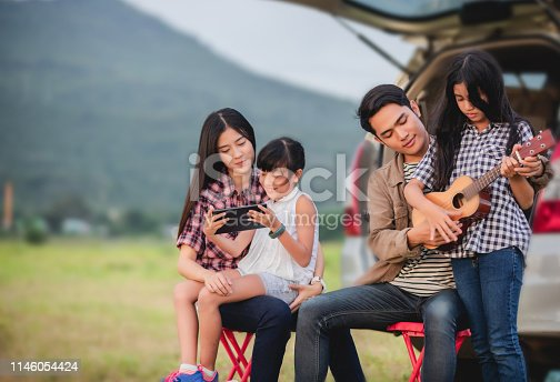 849398784 istock photo happy little girl playing ukulele with asian family sitting in the car for enjoying road trip and summer vacation 1146054424