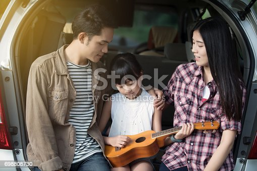 849398784 istock photo happy little girl playing ukulele with asian family sitting in the car for enjoying road trip and summer vacation 698808730