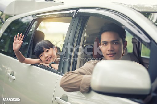 849398784 istock photo happy little girl playing ukulele with asian family sitting in the car for enjoying road trip and summer vacation 698809060