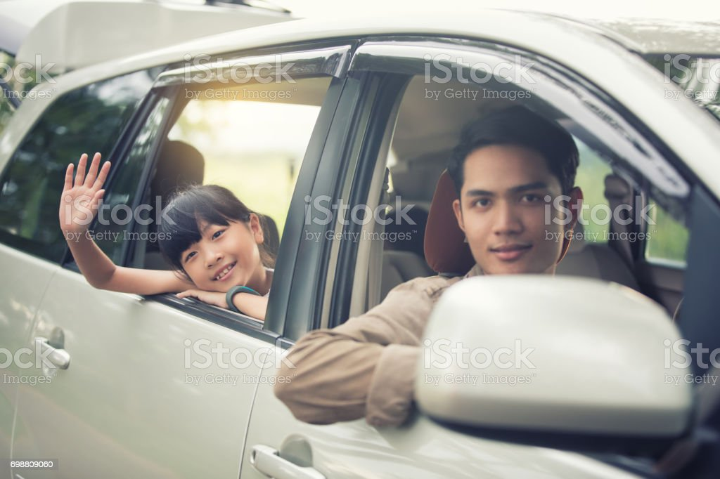happy little girl playing ukulele with asian family sitting in the car for enjoying road trip and summer vacation stock photo