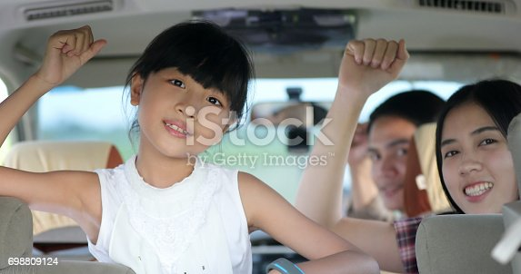 849398784 istock photo happy little girl playing ukulele with asian family sitting in the car for enjoying road trip and summer vacation 698809124