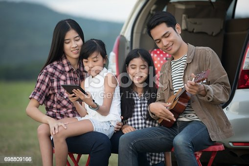 849398784 istock photo happy little girl playing ukulele with asian family sitting in the car for enjoying road trip and summer vacation 698809166