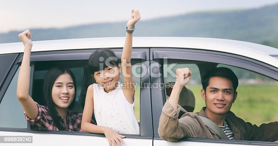 849398784 istock photo happy little girl playing ukulele with asian family sitting in the car for enjoying road trip and summer vacation 698809240