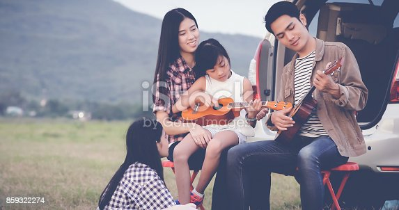 849398784istockphoto happy little girl playing ukulele with asian family sitting in the car for enjoying road trip and summer vacation 859322274