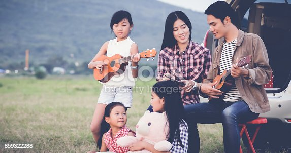 849398784istockphoto happy little girl playing ukulele with asian family sitting in the car for enjoying road trip and summer vacation 859322288