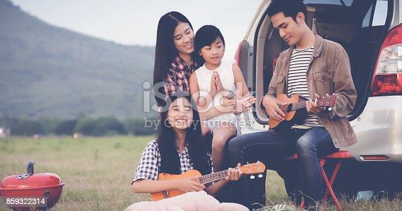 849398784 istock photo happy little girl playing ukulele with asian family sitting in the car for enjoying road trip and summer vacation 859322314