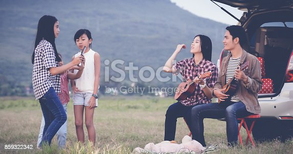 849398784 istock photo happy little girl playing ukulele with asian family sitting in the car for enjoying road trip and summer vacation 859322342