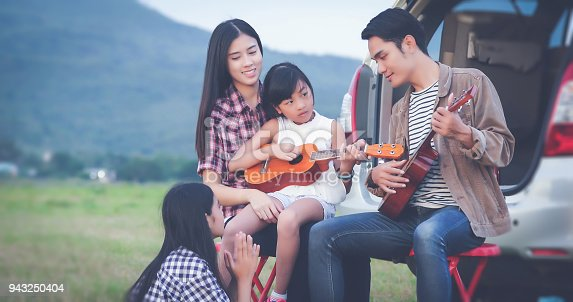 849398784 istock photo happy little girl playing ukulele with asian family sitting in the car for enjoying road trip and summer vacation 943250404