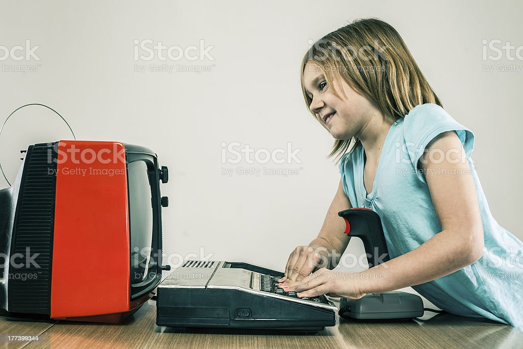 Happy little girl playing vintage video games with retro joystick royalty-free stock photo