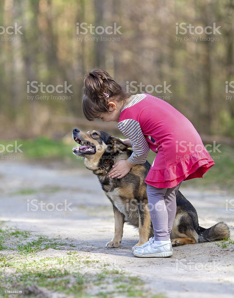 Happy little girl playing with dog royalty-free stock photo