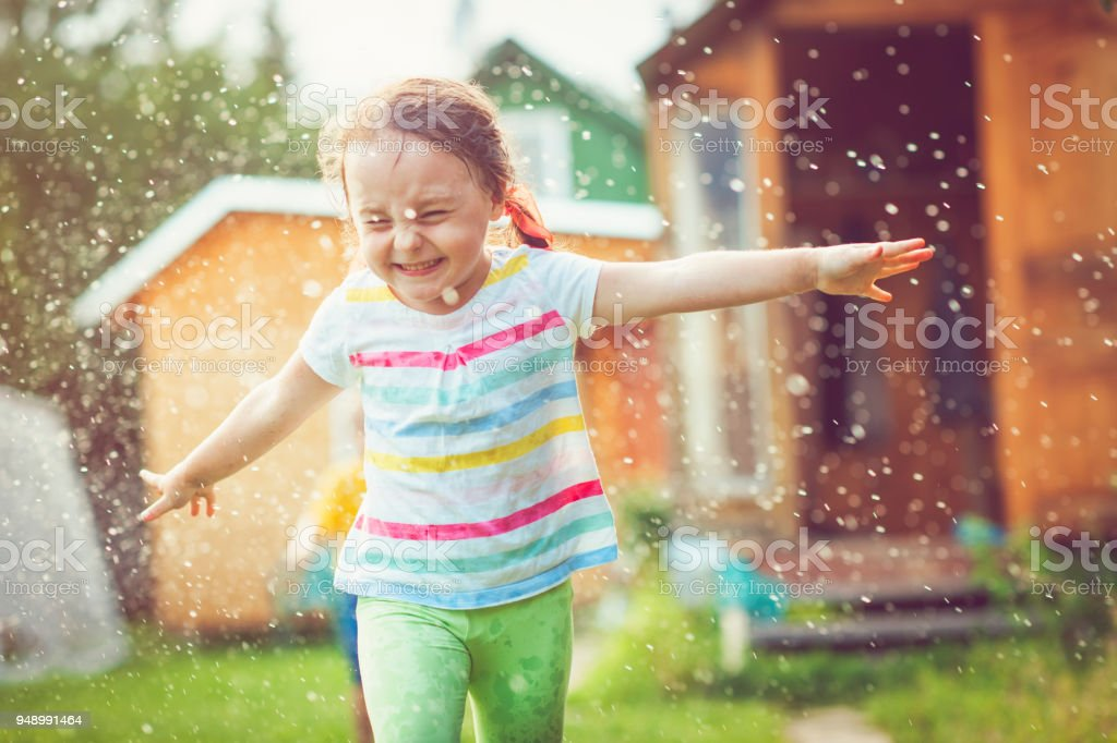 Happy little girl playing with garden sprinkler stock photo