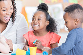 Adorable African American preschooler has fun while playing with modeling clay with her teacher and friends.