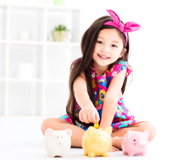 happy little girl playing with piggy bank stock photo