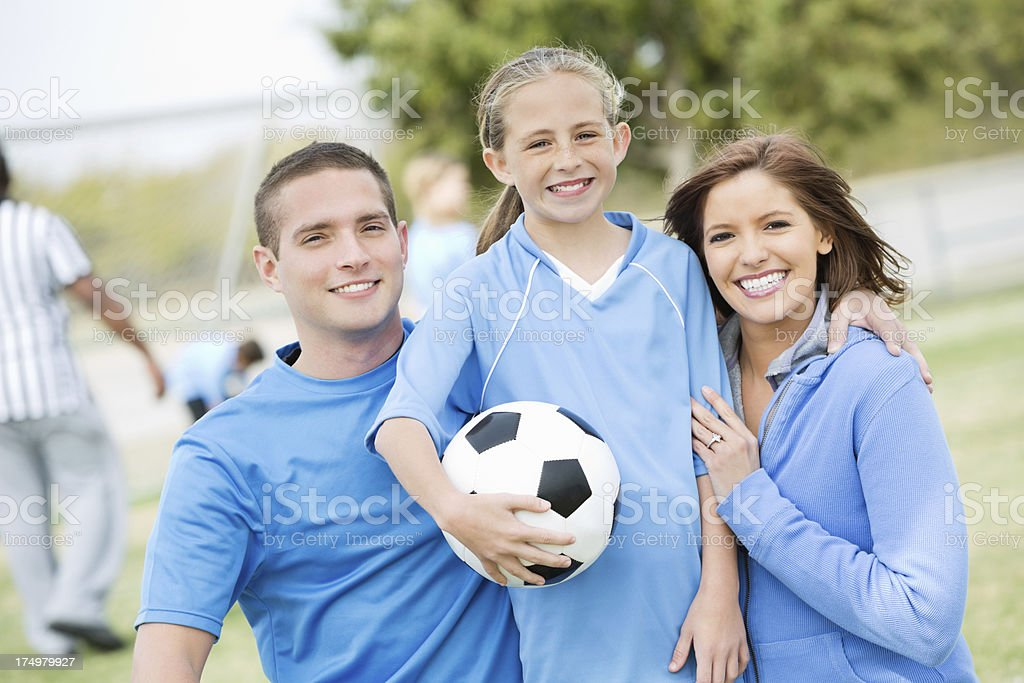 Happy little girl posing with parents at soccer game stock photo