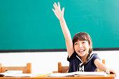 istock happy little girl  raised hands in classroom 819674070