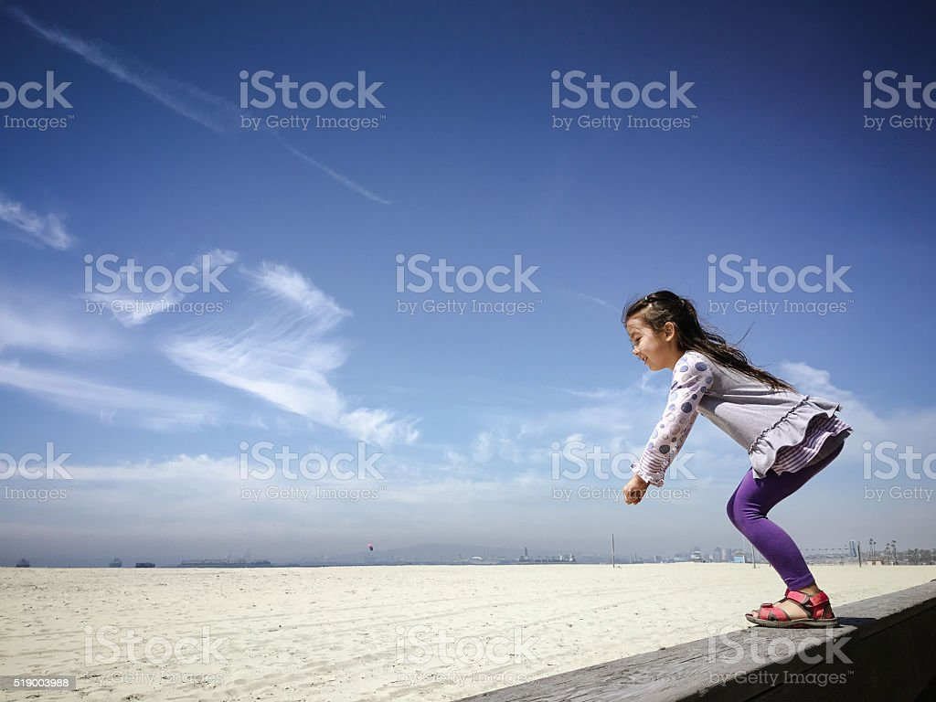 Happy little girl readies herself to jump on sand Happy little girl is ready to jump onto the sand at a beach, with a blue sky in the background. Shot on an iphone 6s plus. She's standing on the edge of the historic wooden boardwalk. This beach is located at Long Beach, CA -- at The Peninsula near Belmont Shore, CA. 6-7 Years Stock Photo
