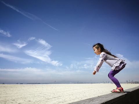 Happy Little Girl Readies Herself To Jump On Sand Stock Photo - Download Image Now