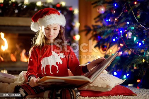 1062609644 istock photo Happy little girl reading a story book by a fireplace in a cozy dark living room on Christmas eve 1057370664