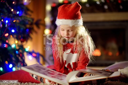 1062609644 istock photo Happy little girl reading a story book by a fireplace in a cozy dark living room on Christmas eve 1062155392