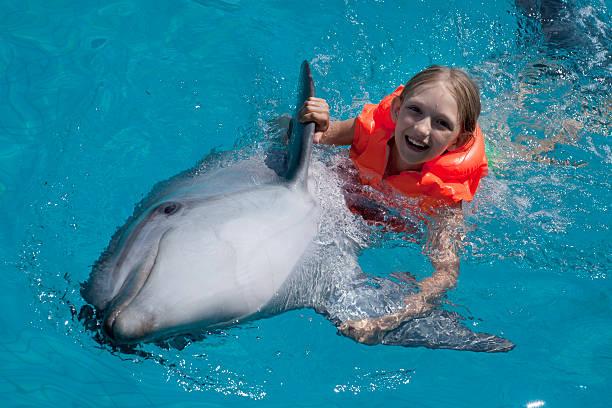 Happy Little Girl Riding den Delfinen im Swimmingpool. – Foto