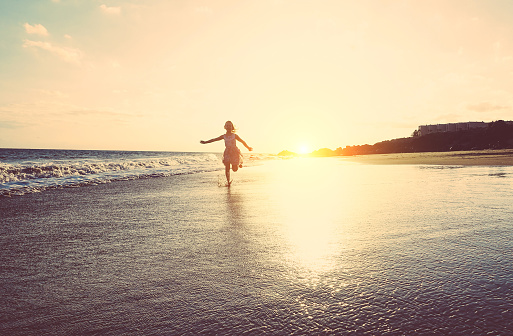 Happy little girl running inside water on the beach at sunset - Kid having fun in holiday vacation - Youth, lifestyle and happiness concept - Vintage filter - Focus on silhouette