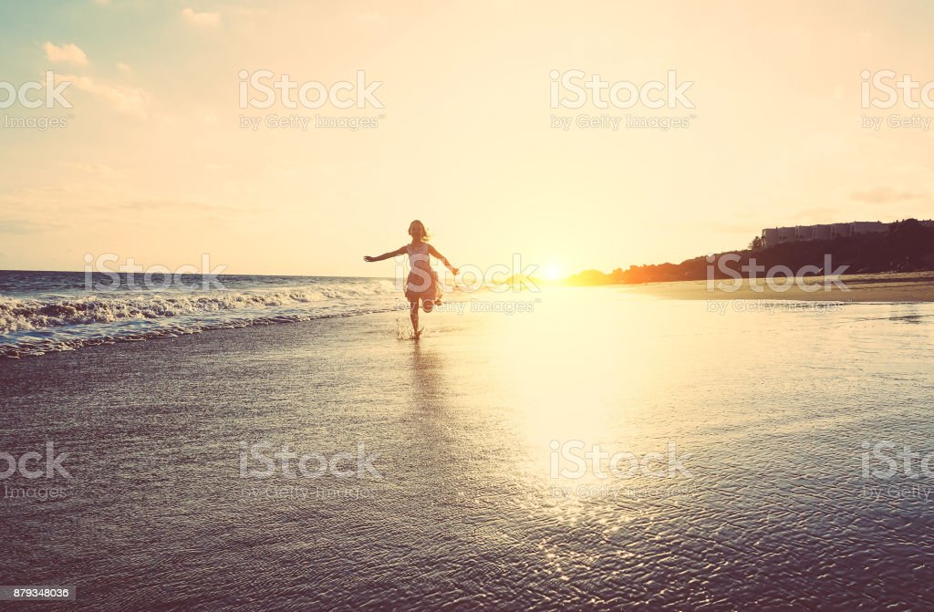 Happy little girl running inside water on the beach at sunset - Kid having fun in holiday vacation - Youth, lifestyle and happiness concept - Vintage filter - Focus on silhouette stock photo