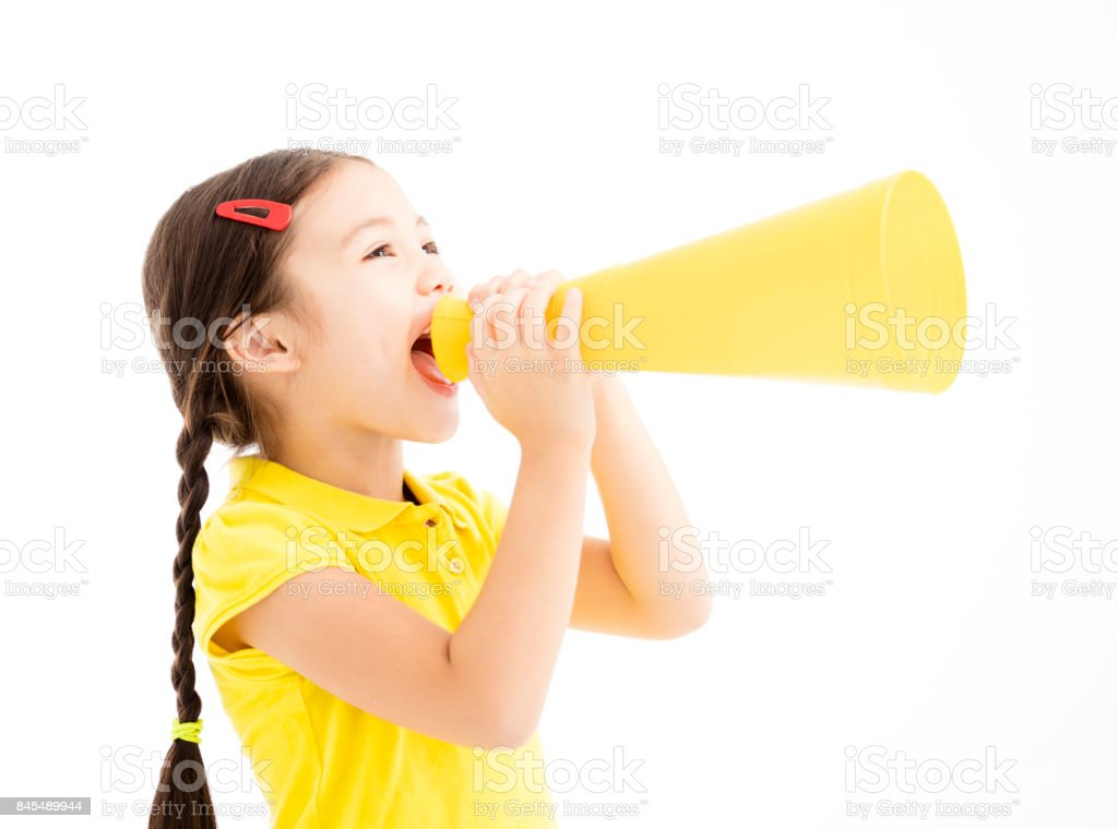 happy little girl shouting by megaphone stock photo
