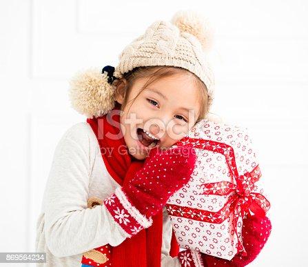 istock happy little girl showing christmas gift 869564234