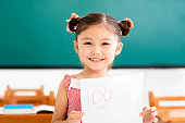 istock happy little girl showing exam paper with a plus in classroom 666510976
