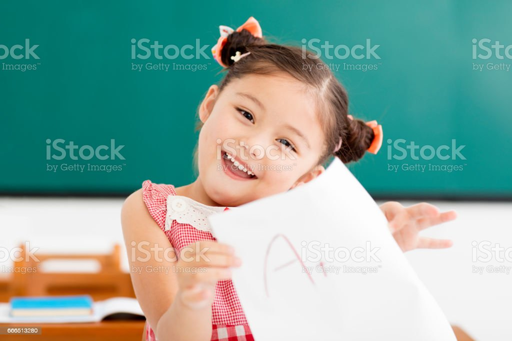happy little girl showing exam paper with a plus in classroom stock photo