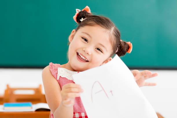menina feliz, mostrando o papel de exame com um plus em sala de aula - happy test results - fotografias e filmes do acervo