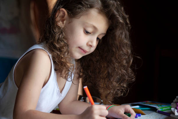 Happy little girl sitting behind the table and drawing with a felt tip pen stock photo