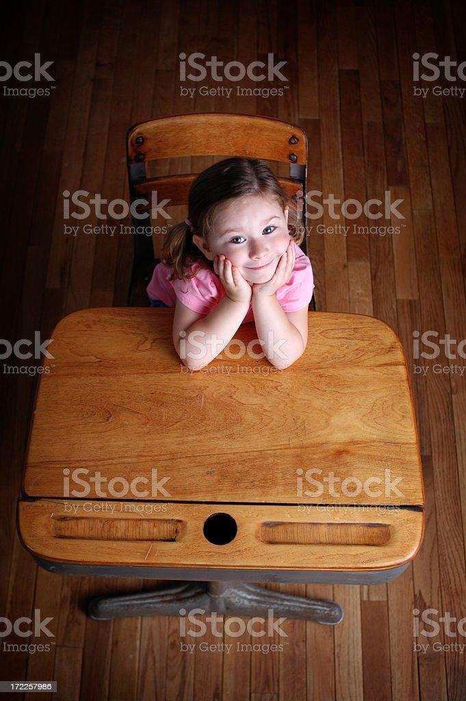Happy Little Girl Sitting in a School Desk royalty-free stock photo