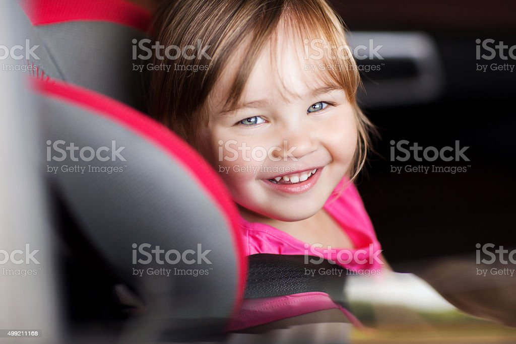 happy little girl sitting in baby car seat stock photo