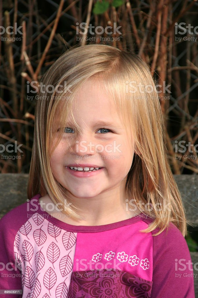 happy little girl sitting on a bench in nature stock photo
